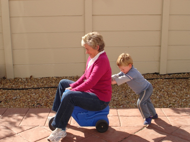 Child_pushing_grandmother_on_plastic_tricycle (1)